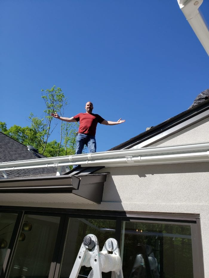 Watchung NJ Home Awning Frame Installation with owner Dana Shaw on roof | Breslow Home Design Center