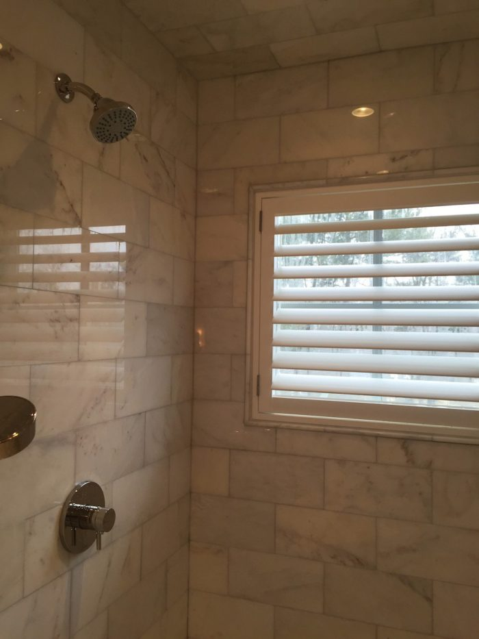 Hunter-Douglas-Palm-Beach-Shutters-Above-Window-Shower-by-Breslow-Home-Design-Center